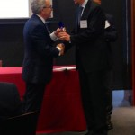 """Fordham University Provost Stephen Freedman, left, congratulates Jarrad Harford of the University of Washington, one of the  """"rising stars"""" honored at a May 6 conference at Fordham."""