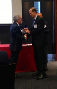 "Fordham University Provost Stephen Freedman, left, congratulates Jarrad Harford of the University of Washington, one of the ""rising stars"" honored at a May 6 conference at Fordham."
